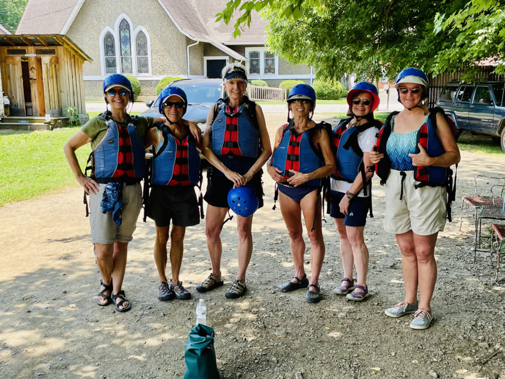 Six women standing with life vests, helmets, getting ready to go rafting.